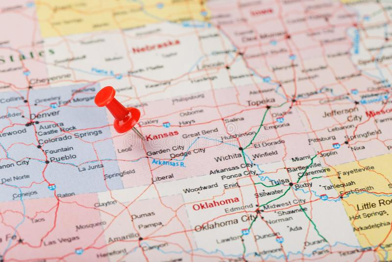 Agulha de escritório vermelha em um mapa dos EUA, do Kansas e do Topeka da capital Mapa ascendente próximo de Kansas com aderênci fotografia de stock
