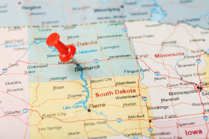 Agulha de escritório vermelha em um mapa de EUA, de North Dakota e da capital Bismarck Mapa North Dakota do close up com aderênci imagem de stock
