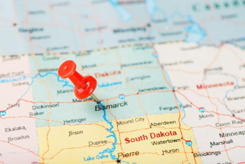 Agulha de escritório vermelha em um mapa de EUA, de North Dakota e da capital Bismarck Mapa North Dakota do close up com aderênci imagem de stock royalty free
