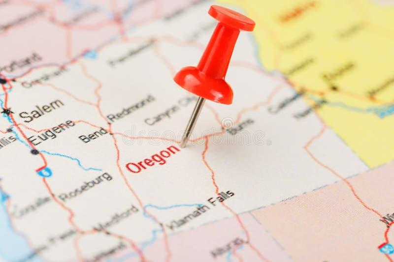 Agulha de escritório vermelha em um mapa de EUA, de Oregon e da capital Salem Mapa Oregon do close up com aderência vermelha imagem de stock