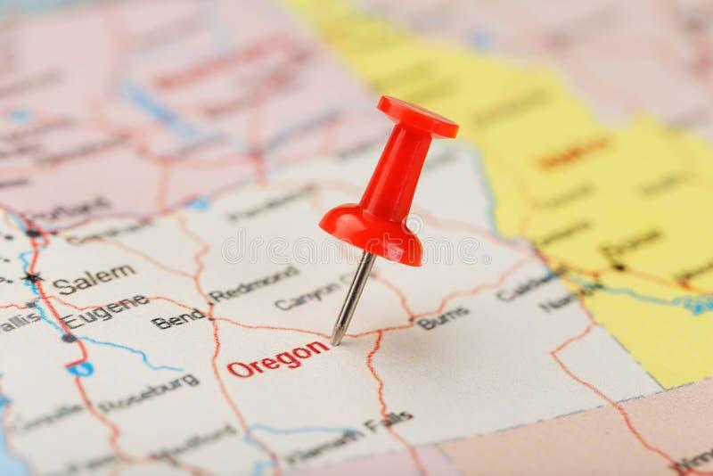 Agulha de escritório vermelha em um mapa de EUA, de Oregon e da capital Salem Mapa Oregon do close up com aderência vermelha fotos de stock royalty free