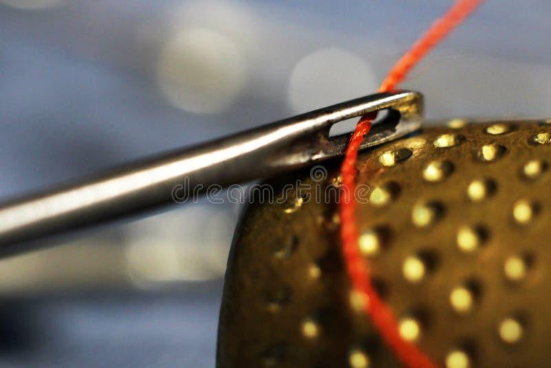 Agulha e linha vermelha completamente, dedal do ouro fotografia de stock