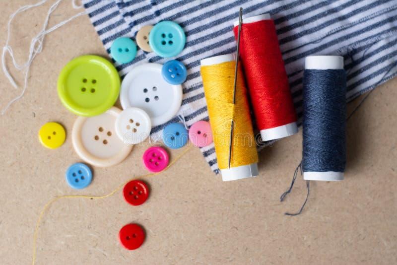 A agulha, os botões e a linha estão no algodão imagens de stock royalty free