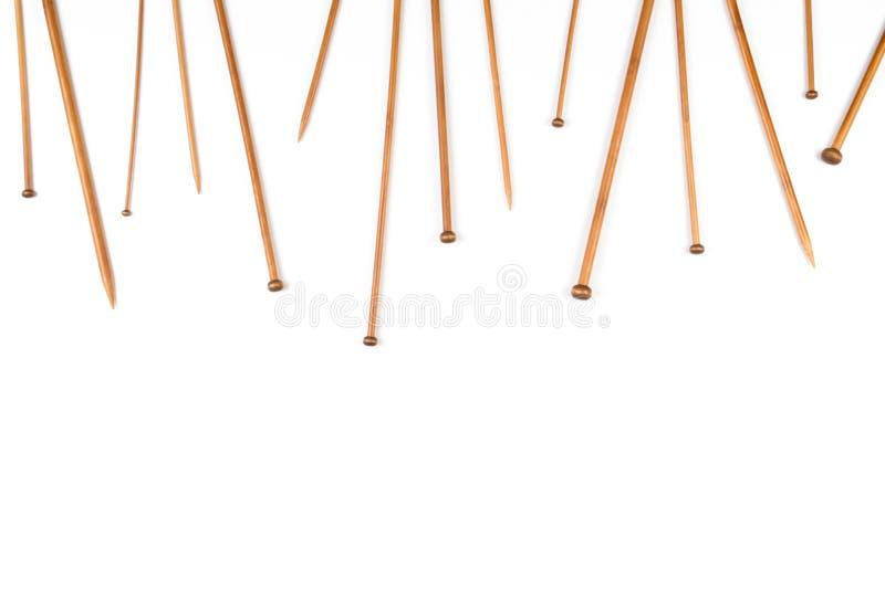 Agulhas de confecção de malhas de bambu de madeira arranjadas como a beira do quadro no fundo branco foto de stock