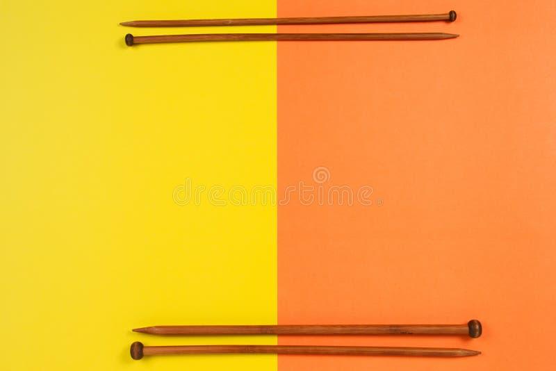 Agulhas de confecção de malhas de madeira de Brown arranjadas como a beira do quadro no fundo amarelo e alaranjado fotos de stock royalty free