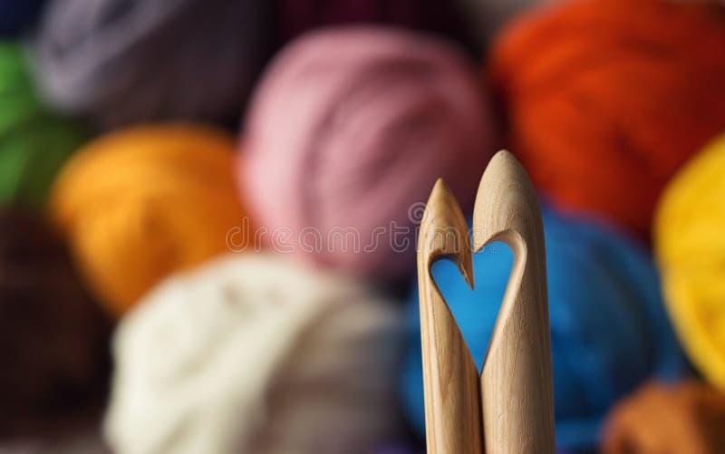 Agulhas de confecção de malhas de madeira no fundo de vagabundos coloridos de lãs do merino fotografia de stock royalty free