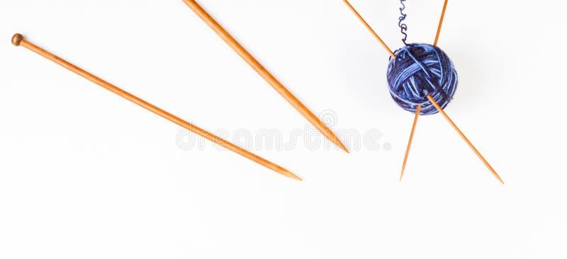 Agulhas de confecção de malhas e bola de bambu de madeira do fio no fundo branco da bandeira fotos de stock