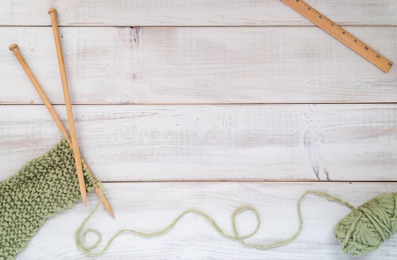 Agulhas, fio e régua de confecção de malhas em uma tabela de madeira whitewashed imagem de stock