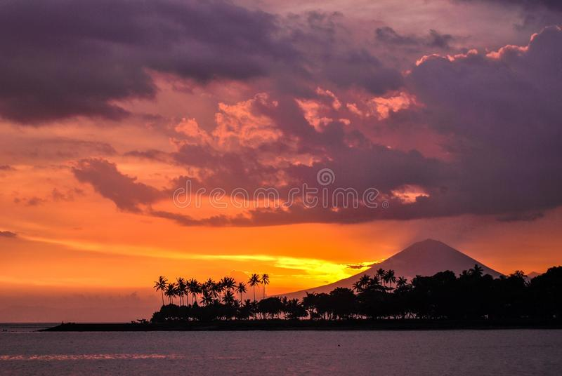 Agung Volcano during sunset time. Sunrise over Volcano Agung situated in Bali, seen from neighboring Lombok island