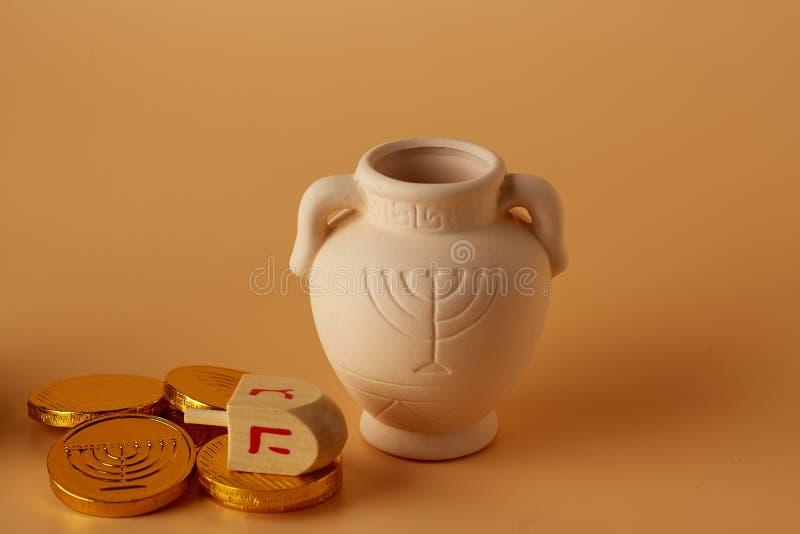 Ah gelt, pieniądze lub monety z Hanukkah dreidel i Hanukkah gliny dzbankiem Przekład: Szczęśliwi wakacje zdjęcia stock