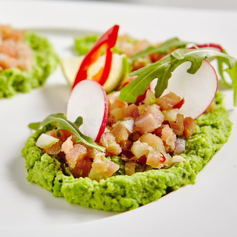 Ahi Tuna Seviche mit Rettich-Scheiben und Rucola auf weißer Platte stockfotos