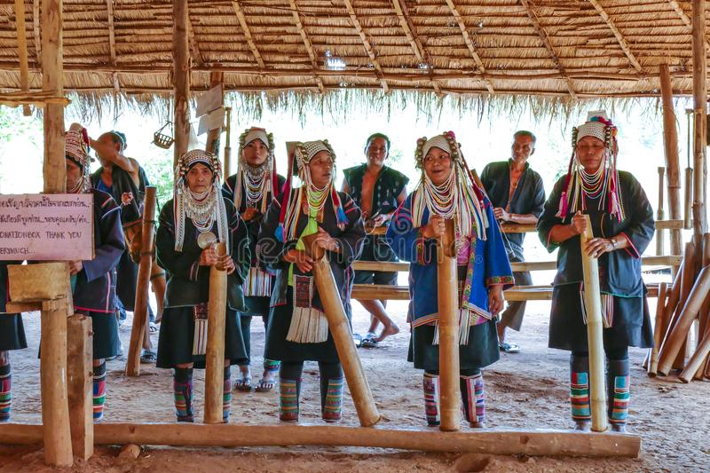 AHKA Hill Tribe Folklore, Northern Thailand. A group of Akha women and a men in a mountain village with traditional dress and headgear, played with traditional stock photography
