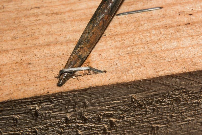 Ahle verbiegt die Metallklammer weg vom Brett stockfotos