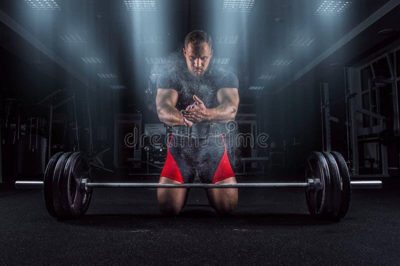 Ahlete klęczy w gym i klascze jego ręki po czym dus zdjęcia stock