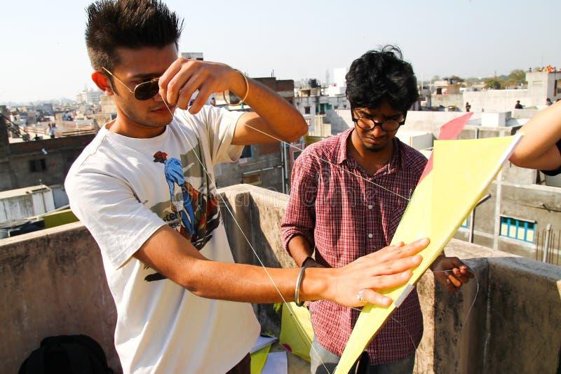 Ahmenabad, India - 8 januari 2017: de jonge jongens verzamelen zich boven daken voorbereidingen treffend om te vieren traditionee stock foto's