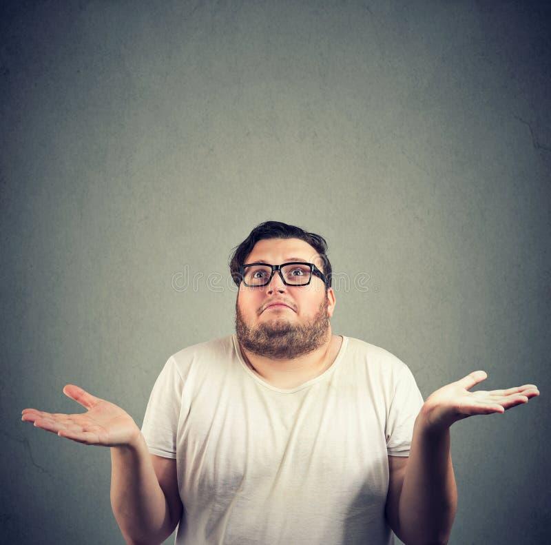 Ahnungsloser Mann, der seine Schultern zuckt stockfotos
