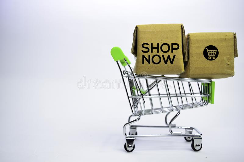 Ahora hace compras el texto en pequeñas cajas y carro de la compra Conceptos sobre compras en l?nea Aislado en el fondo blanco foto de archivo libre de regalías