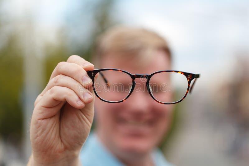 Ahora puedo verle bien Hombre joven hermoso que sostiene los vidrios y que mira a través de ellos imagenes de archivo