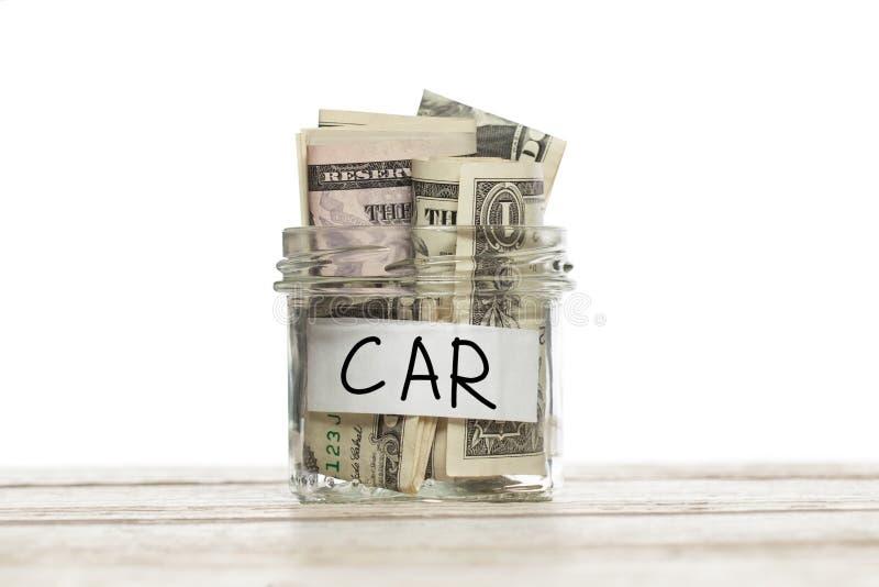 Ahorrándodólar dinero para el coche en el tarro de cristal en la tabla de madera contra el fondo blanco fotografía de archivo