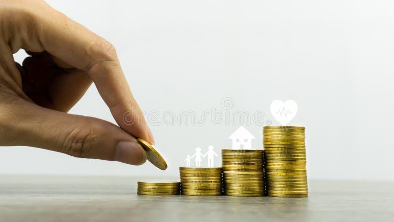 Ahorrando o haciendo el dinero para la vida familiar en el concepto futuro Una mano del hombre que pone la moneda en la pila de l fotografía de archivo