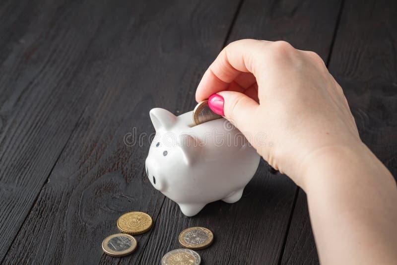 Ahorre el concepto del dinero, hucha en una mano humana imágenes de archivo libres de regalías