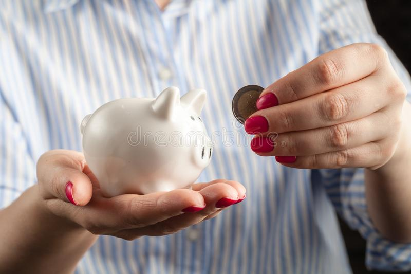 Ahorre el concepto del dinero, hucha en una mano humana fotos de archivo libres de regalías