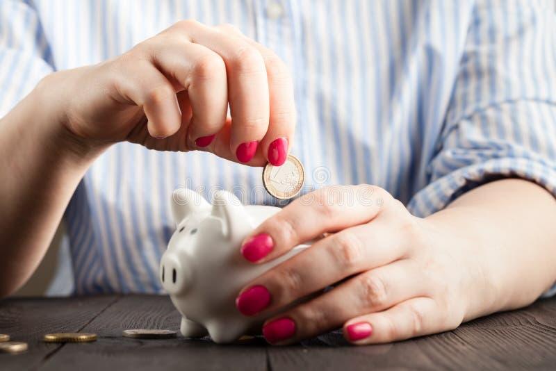 Ahorre el concepto del dinero, hucha en una mano humana imagen de archivo
