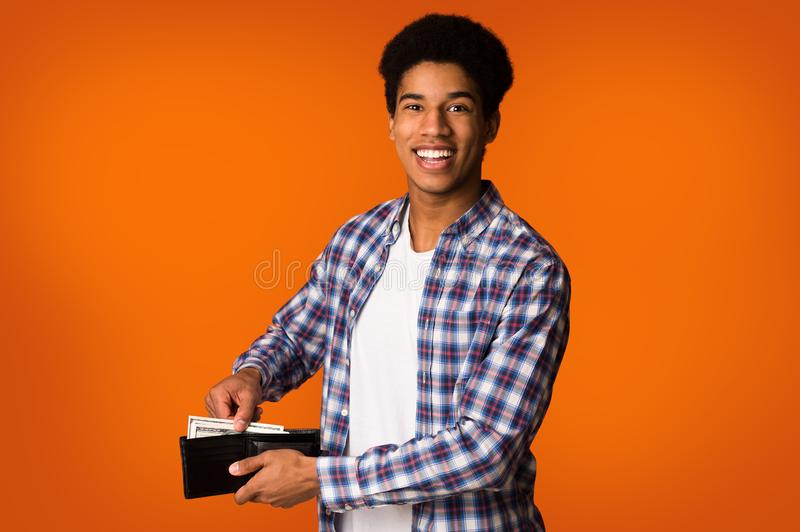 ahorro del dinero Individuo afroamericano que pone billetes de banco en la cartera fotografía de archivo libre de regalías