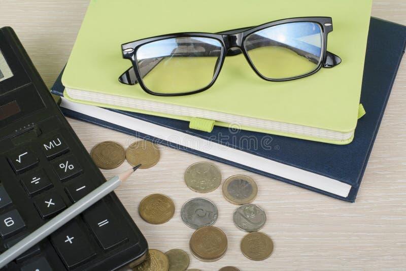 Ahorros caseros, concepto del presupuesto Libreta, calculadora, lápiz, lentes y monedas en la tabla de madera del escritorio de o imagen de archivo