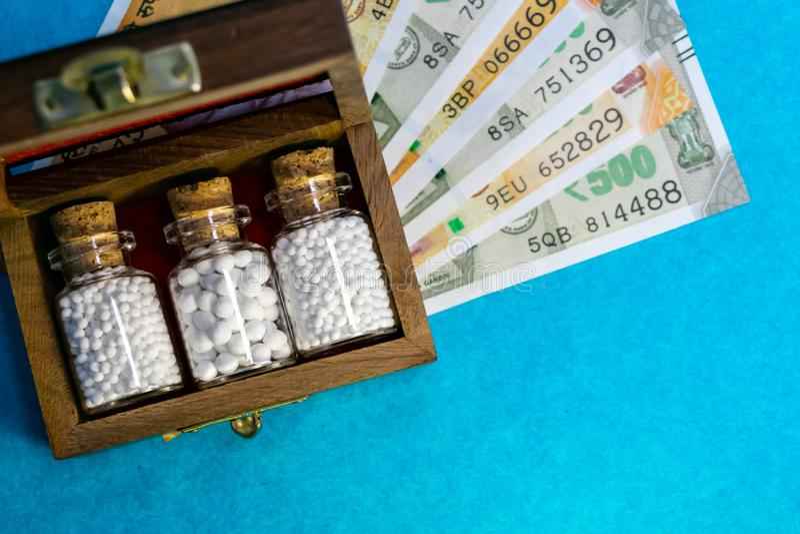 Ahorros con - dinero y concepto homeopático - la caja vieja de madera homeopahy con la medicina homeopática de las botellas de cr foto de archivo
