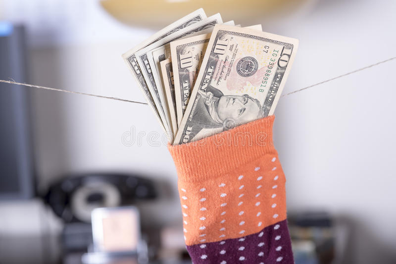 Ahorros del dólar ocultados en un calcetín imagenes de archivo