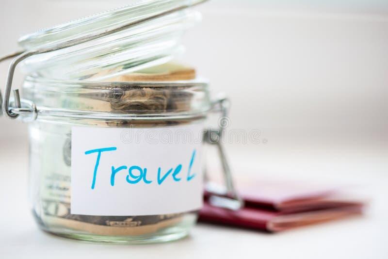 Ahorros del dinero de los días de fiesta en un tarro de cristal Dos pasaportes están al lado de caja de dinero imágenes de archivo libres de regalías