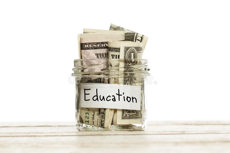Ahorros del efectivo del dinero para la educación en la tabla de madera contra el fondo blanco Tarro de cristal con dólar para la imágenes de archivo libres de regalías