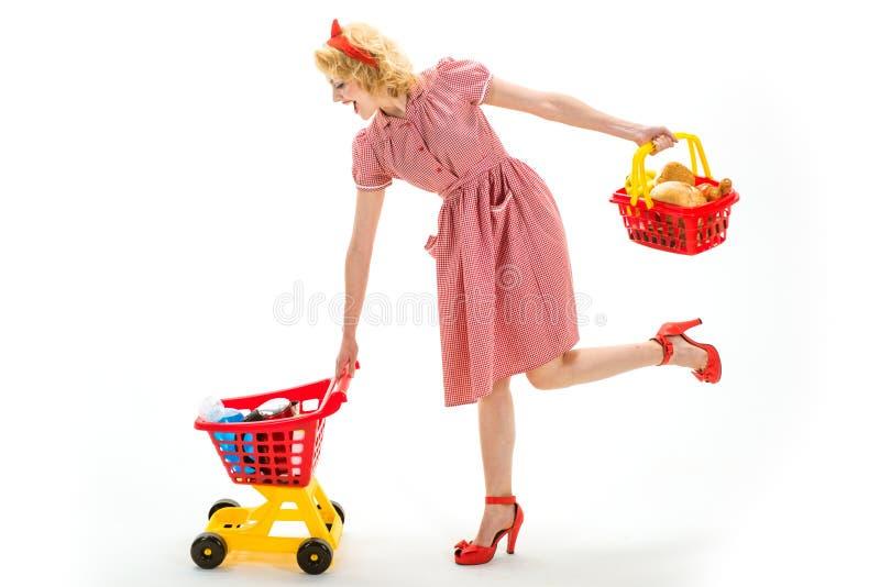 Ahorros en compra Servicio a domicilio la mujer retra feliz va a hacer compras mujer del ama de casa del vintage aislada en blanc fotografía de archivo