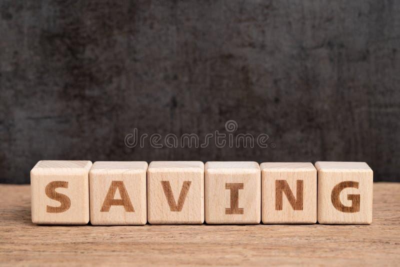 Ahorros felices, presupuesto, inversión o concepto financiero de las metas, pila de ahorro de madera de la palabra del edificio d fotos de archivo libres de regalías