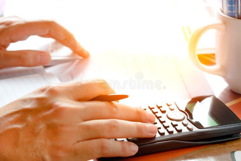 Ahorros, finanzas, economía y concepto casero - cercanos para arriba de hombre con la calculadora que cuenta haciendo notas en ca fotografía de archivo