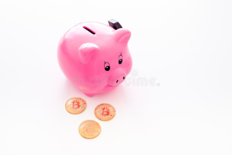 ahorros Moneybox en la forma del cerdo cerca de monedas en el espacio blanco de la copia del fondo fotografía de archivo