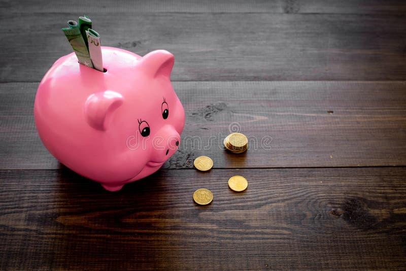 ahorros Moneybox en la forma del cerdo con los billetes de banco que caen en ella cerca de monedas en el espacio de madera oscuro foto de archivo