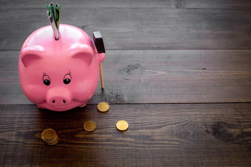 ahorros Moneybox en la forma del cerdo con los billetes de banco que caen en ella cerca de monedas en el espacio de madera oscuro fotos de archivo libres de regalías