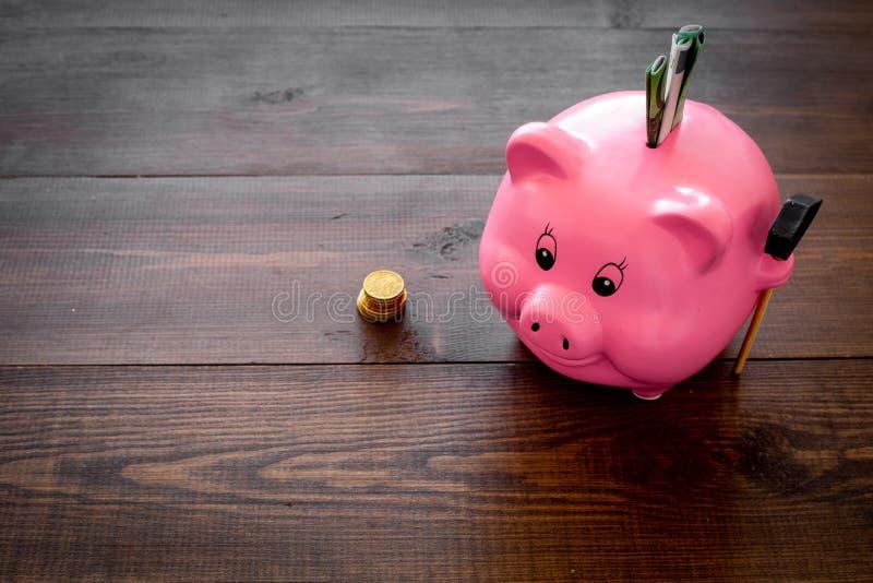 ahorros Moneybox en la forma del cerdo con los billetes de banco que caen en ella cerca de monedas en espacio de madera oscuro de imagenes de archivo