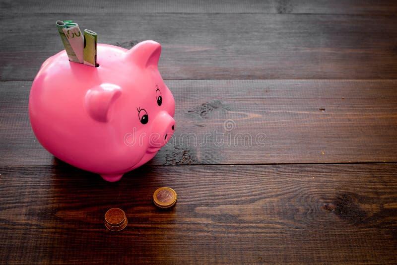 ahorros Moneybox en la forma del cerdo con los billetes de banco que caen en ella cerca de monedas en espacio de madera oscuro de fotografía de archivo libre de regalías