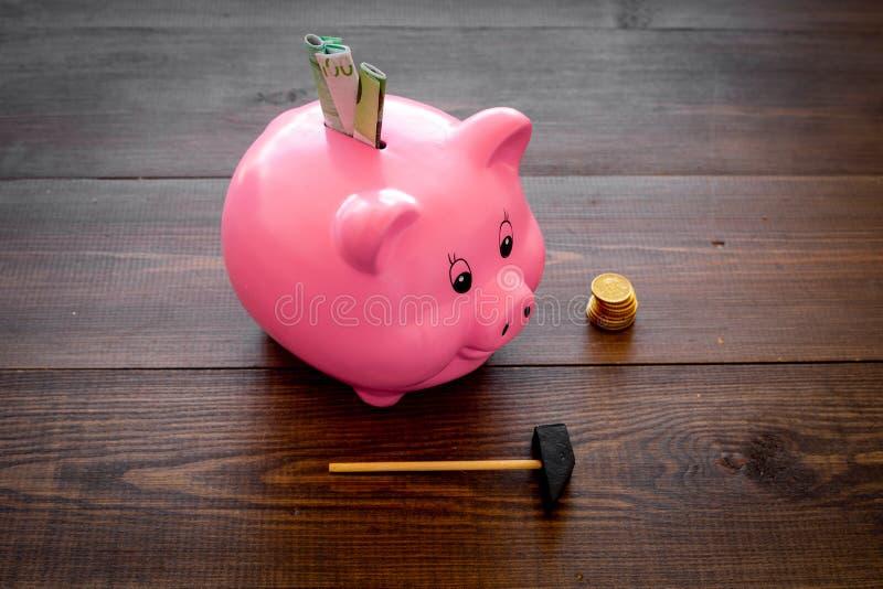 ahorros Moneybox en la forma del cerdo con los billetes de banco que caen en ella cerca de monedas y del martillo en copia de mad imagenes de archivo