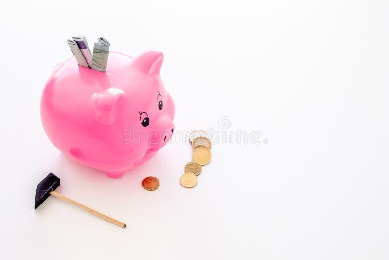 ahorros Moneybox en la forma del cerdo con los billetes de banco que caen en ella cerca de monedas y del martillo en el espacio b fotos de archivo