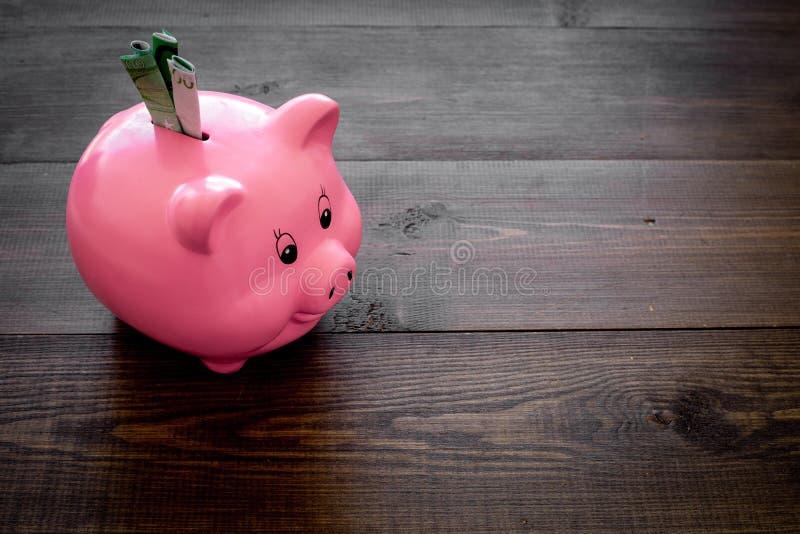ahorros Moneybox en la forma del cerdo con los billetes de banco que caen en ella en el espacio de madera oscuro del fondo para e foto de archivo