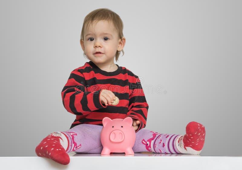 Ahorros y concepto de las actividades bancarias La muchacha del niño está poniendo monedas en el banco guarro del dinero fotografía de archivo libre de regalías