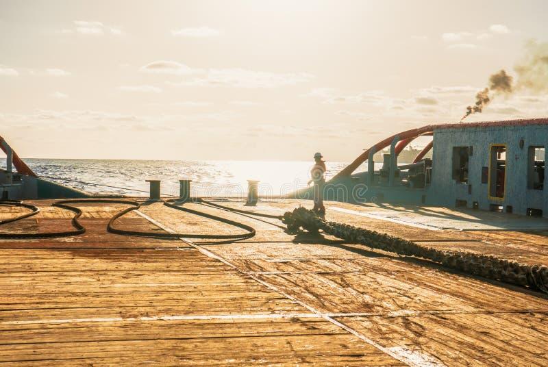 AHTS船乘员组船拖曳导线为静态拖曳罐车举做准备 免版税库存照片