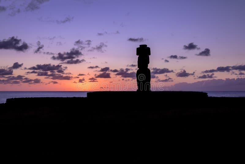 Ahu Tahai Moai Statue silhouette wearing topknot at sunset near Hanga Roa - Easter Island, Chile. Ahu Tahai Moai Statue silhouette wearing topknot at sunset near stock photo