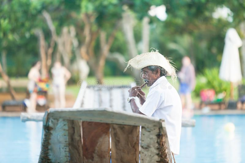 Ahungalla, Sri Lanka - An old native flute player sitting on traditional longboat royalty free stock photography