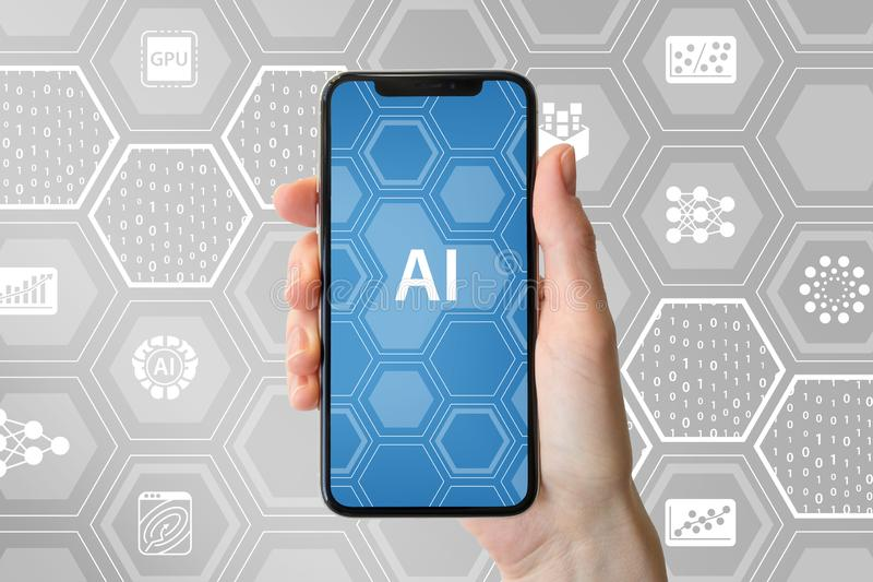 AI / artificial intelligence concept. Hand holding modern frameless smartphone in front of neutral background with icons royalty free stock photo