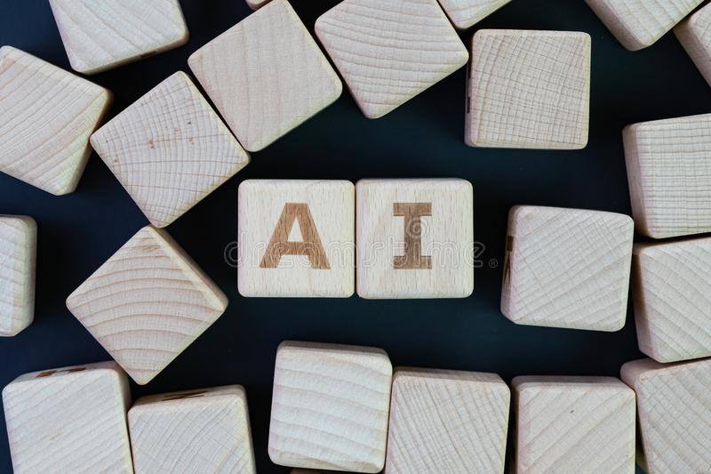 AI, Artificial Intelligence or machine learning in future world concept, straggle cube wooden blocks with some combine the word AI. On dark black chalkboard stock photography